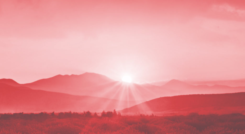 Image of a sunrise over mountains with a red filter.